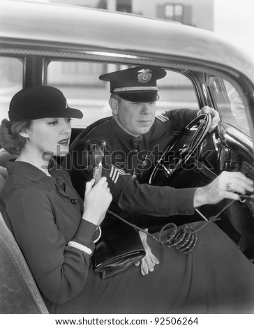 Woman sitting next to a policeman in his car holding a microphone in her hand - stock photo