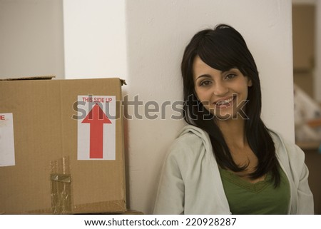 Woman sitting next to moving box - stock photo