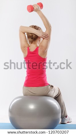 Woman sitting on a ball and doing exercise with dumbbells view from the back - stock photo