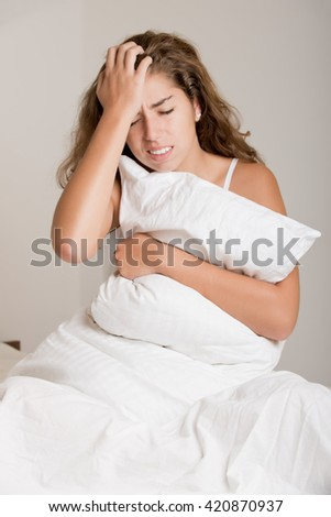 Woman sitting on a bed, waking up, isolated in white - stock photo
