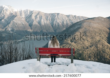 woman sitting on a bench and looked at the panorama of mountains - stock photo