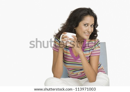 Woman sitting on a chair and drinking tea - stock photo