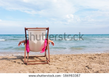 WOman sitting on a chair on the beach - stock photo