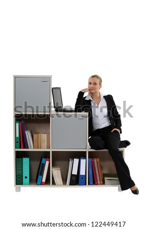 Woman sitting on a modern bookcase - stock photo