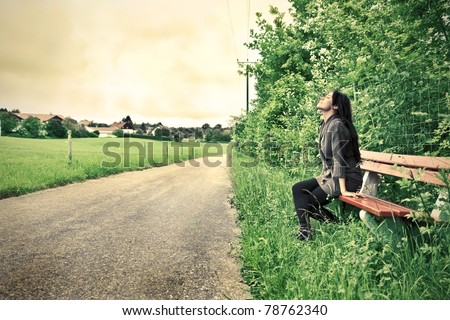 Woman sitting on a park bench near a countryside road - stock photo
