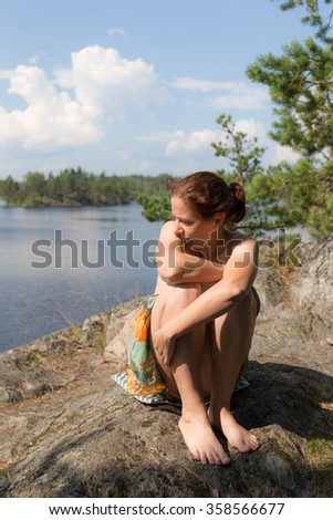 woman sitting on a rock at the forest lake - stock photo