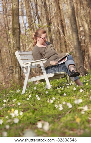 Woman sitting on a sofa in the wood in springtime. She is reading a magazine in the sunlight - stock photo