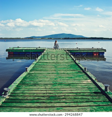Woman sitting on a wooden jetty enjoying the sunshine with arms up. Woman on a pier on the lake greeting the sun with arms wide open. - stock photo