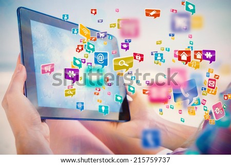 Woman sitting on beach in deck chair using tablet pc showing colourful computer applications - stock photo