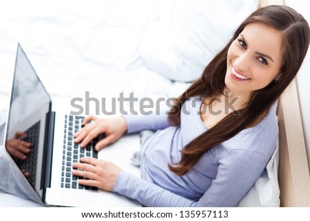 Woman sitting on bed with laptop - stock photo