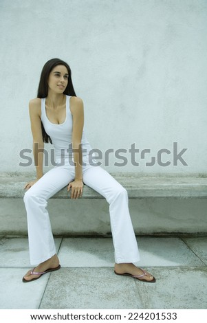 Woman sitting on bench, full length portrait - stock photo