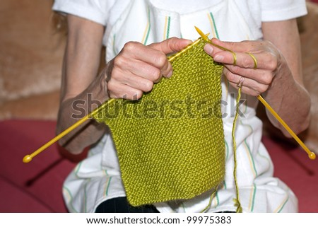woman sitting on couch and knitting wool - stock photo