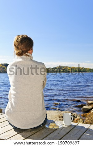Woman sitting on dock relaxing by beautiful lake in Algonquin Park, Canada. - stock photo
