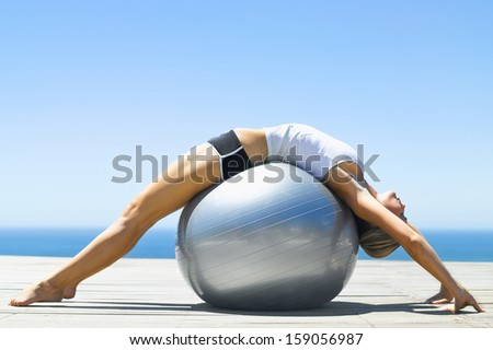 woman sitting on exercise ball - stock photo