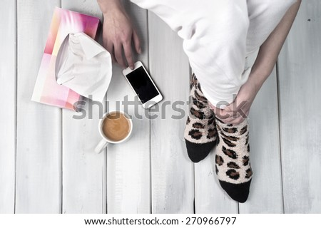 Woman sitting on floor with coffee smartphone and tissue box next to her - stock photo