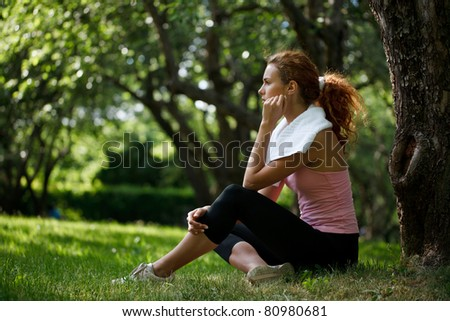 Woman sitting on grass - stock photo