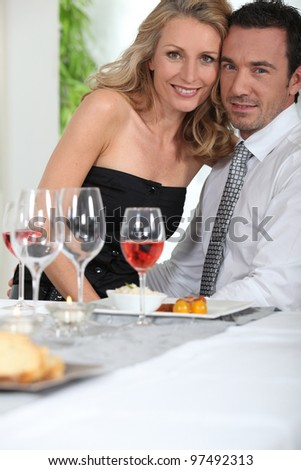 Woman sitting on her partner - stock photo