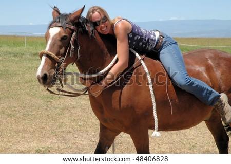 Woman sitting on horse bareback - stock photo