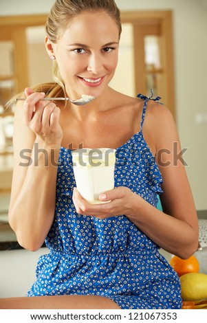 Woman Sitting On Kitchen Counter Eating Ice Cream - stock photo