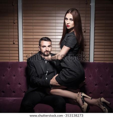 Woman sitting on man. Passion between lovers. Girl sitting on boy. Girl strangling boy. - stock photo