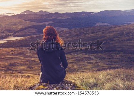 Woman sitting on mountain top and contemplating the sunset - stock photo