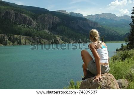 Woman sitting on rock by lake - stock photo