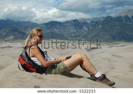 Woman sitting on sand dune - stock photo