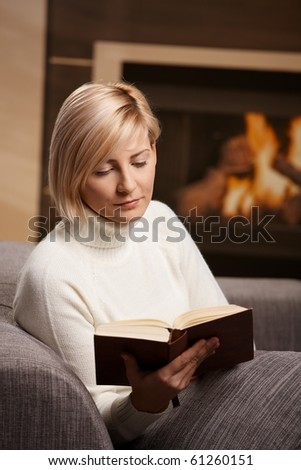 Woman sitting on sofa at home reading book, looking down. - stock photo