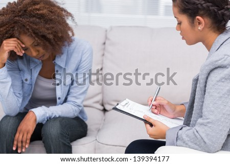 Woman sitting on sofa at therapy with doctor taking notes - stock photo