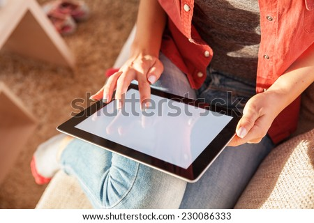 Woman sitting on sofa in living room and using a tablet. - stock photo