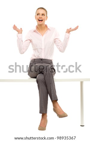 Woman sitting on table with laptop - stock photo
