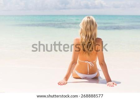 Woman sitting on the beach - stock photo