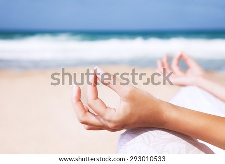 Woman sitting on the beach in lotus pose and meditating, body part, doing yoga exercise outdoors, zen balance and relaxation concept - stock photo