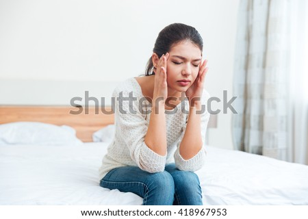 Woman sitting on the bed with headache at home - stock photo
