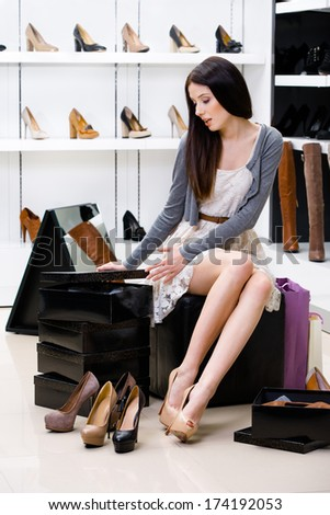Woman sitting on the chair and trying on pumps in the shop can't decide what to buy - stock photo