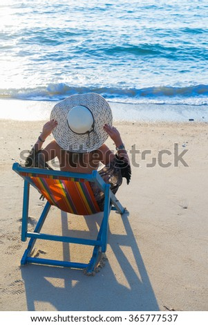 Woman sitting on the lounge chair at the tropical beach  - stock photo