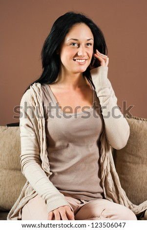 Woman sitting on the sofa and talking on the phone,Woman with mobile phone - stock photo