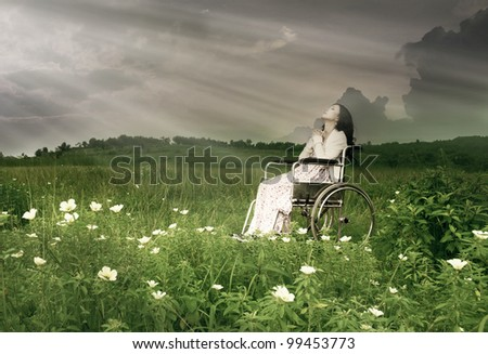 Woman sitting on wheelchair is praying. Shot in meadow - stock photo