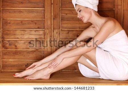 Woman sitting on wooden bench, relaxing in sauna at health spa center. - stock photo