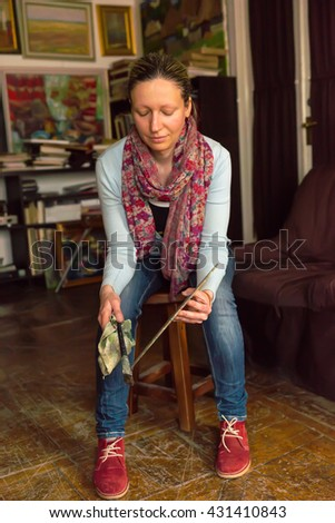 Woman sitting painting in a studio or gallery holding a colorful artists palette and paintbrush in her hand - stock photo