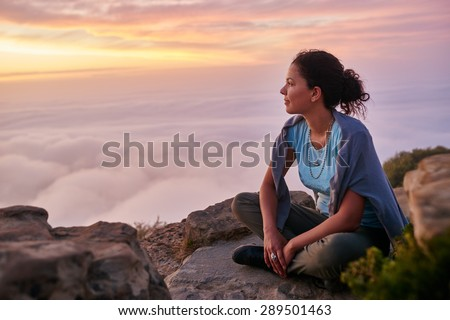 Woman sitting serenely on a mountain top at sunrise looking at the low-lying clouds and sky - stock photo