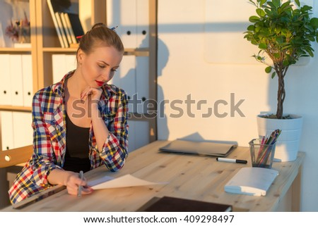 Woman sitting thoughtful, concentrated, writing, reading, working at light studio. Side view portrait of a young student thinking holding paper and pen. - stock photo