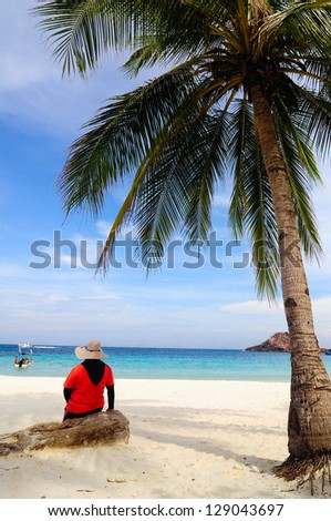 Woman sitting underneath a palm at a beach - stock photo
