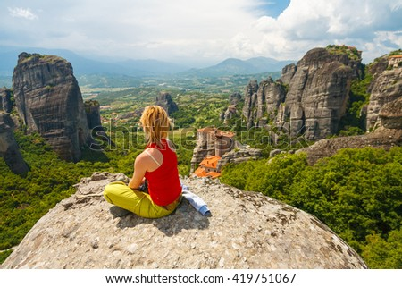 Woman sitting with back to camera observing great scenic and  meditative view from the top of a rock in Meteora, Greece - stock photo