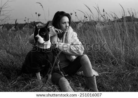 woman sitting with staffordshire terrier in fields behind country town - stock photo