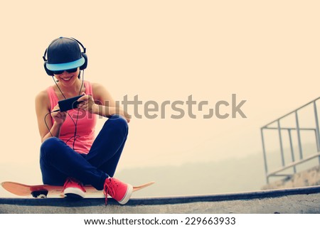 woman skateboarder listening music from cellphone mp3 player on skatepark  - stock photo