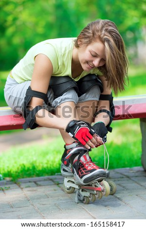 Woman skating in park. Girl going rollerblading sitting on bench  putting on inline skates. Sporty caucasian woman in outdoor fitness activities.  - stock photo