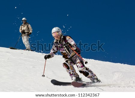Woman skier descends the steep slope in deep snow in the sun. Couple man and woman in the mountains - stock photo