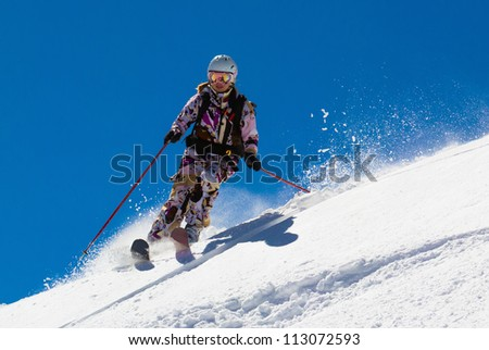 Woman skier in the deep dreams against a bright cloudless sky - stock photo