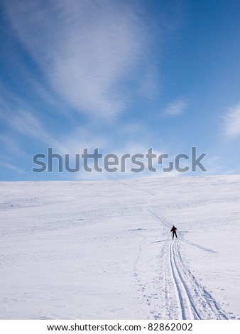 Woman skiing alone down a light hillside in the norwegian mountains at easter - stock photo